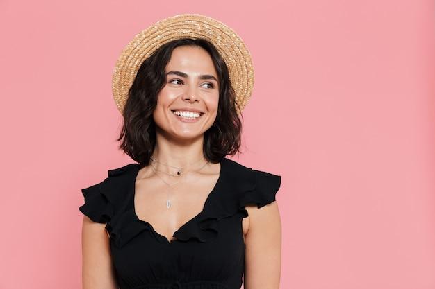 Jovem alegre com um vestido de verão em pé, isolada na parede rosa, olhando para longe