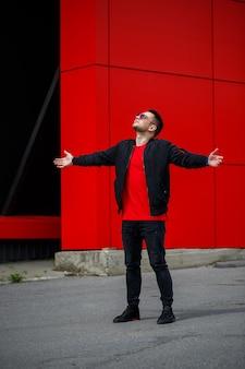 Jovem alegre com uma barba com um sorriso positivo em uma camiseta com uma jaqueta preta da moda em uma camiseta se passando perto de um prédio de metal vermelho na cidade. feliz cara urbano na rua. roupa para homem