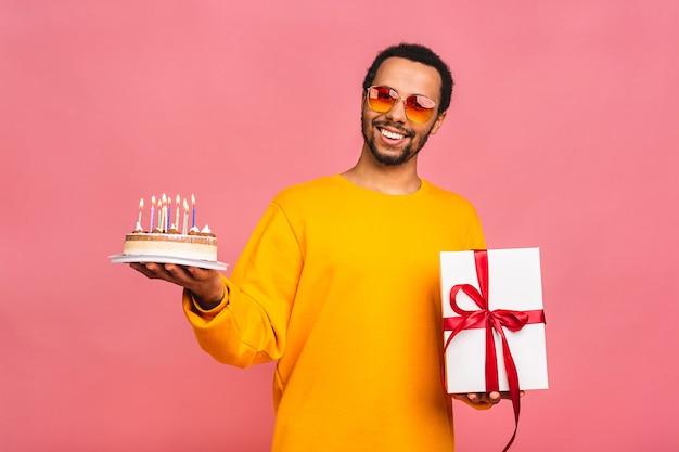 Jovem alegre com uma caixa de presente soprando velas em um bolo de aniversário isolado em rosa.