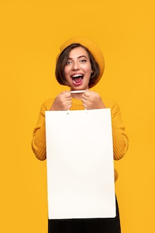 Jovem alegre com uma sacola de compras branca