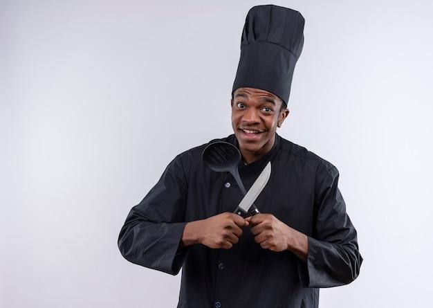 Jovem alegre cozinheira afro-americana com uniforme de chef segurando uma faca e uma espátula isoladas na parede branca