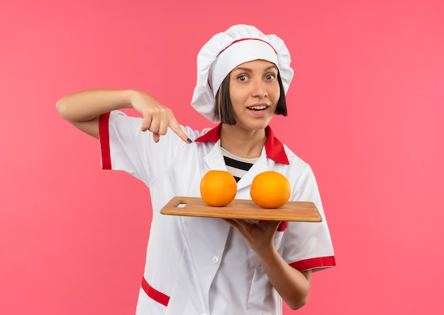 Jovem alegre cozinheira em uniforme de chef segurando e apontando para a placa de corte com laranjas isoladas em rosa