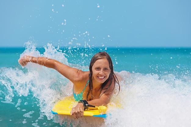Jovem alegre de bodyboard se diverte nas ondas do mar.