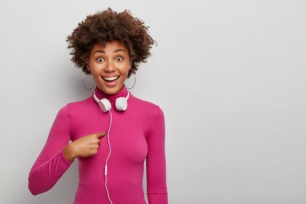 Jovem alegre de cabelos cacheados apontando para si mesma, usando fones de ouvido estéreo
