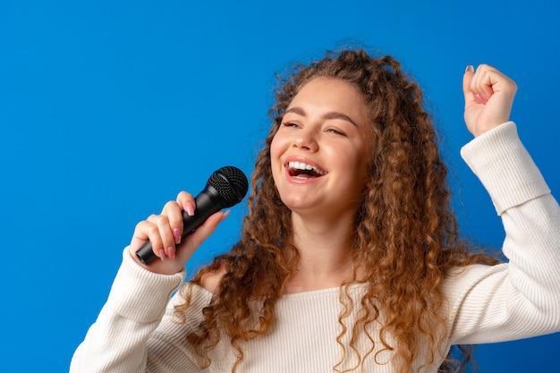 Jovem alegre de cabelos cacheados cantando no microfone contra um fundo azul