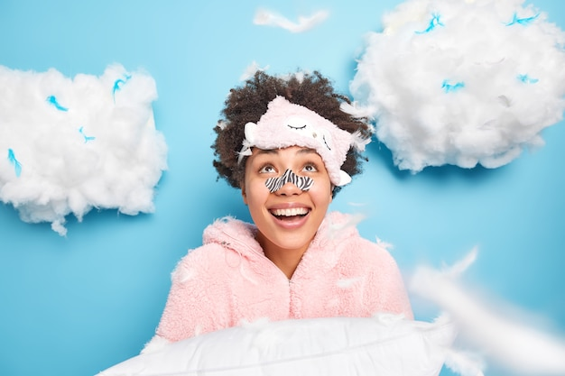 Jovem alegre de cabelos cacheados usa máscara de aplicador no nariz, vestida de pijama, olha alegremente acima de sorrisos amplamente segura travesseiro se prepara para dormir e descansar isolado sobre a parede azul