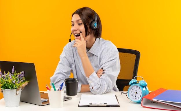 Jovem alegre de call center usando fone de ouvido, sentada na mesa, colocando a mão no queixo, olhando para o laptop isolado em laranja