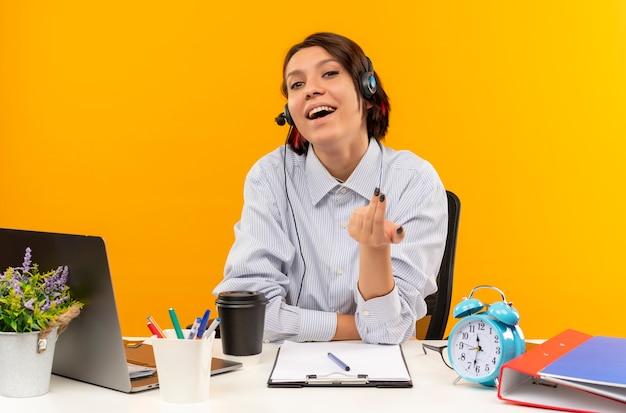 Jovem alegre de call center usando fone de ouvido, sentada na mesa, fazendo gesto de venha cá isolado em laranja