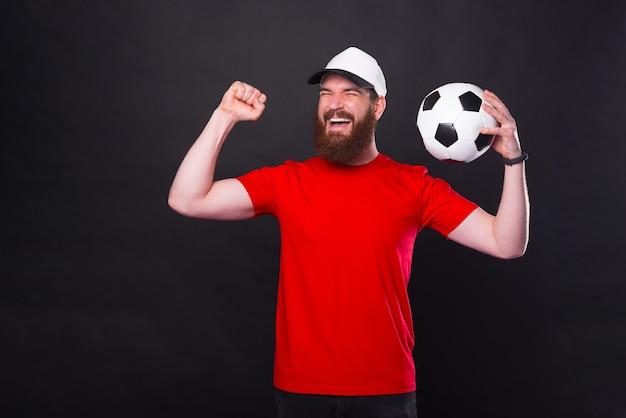 Jovem alegre de camiseta vermelha segurando uma bola de futebol e comemorar a vitória