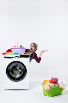 Jovem alegre de frente para o avental sentado atrás do cesto de roupa suja da máquina de lavar no fundo branco