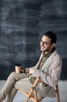 Jovem alegre de óculos e smart casual bebendo enquanto está sentado na cadeira em frente à câmera, isolado