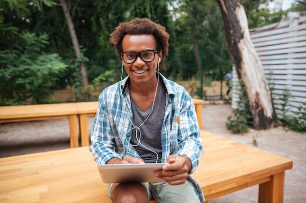 Jovem alegre de óculos usando tablet e sorrindo no parque