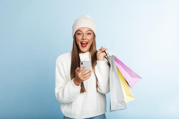 Jovem alegre de suéter, segurando um celular, carregando sacolas de compras