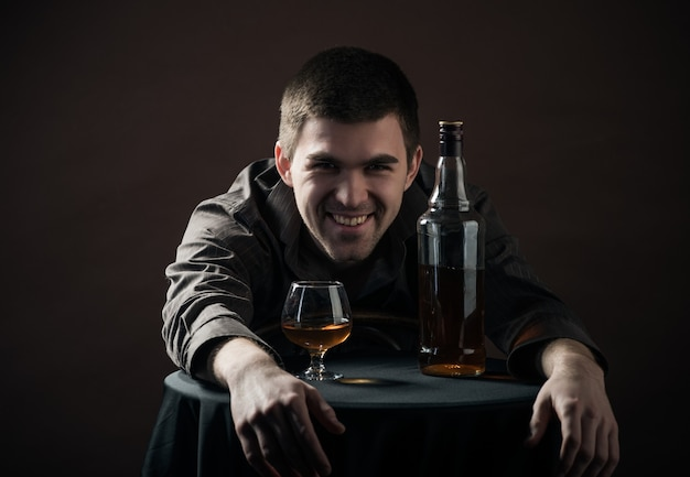 Jovem alegre deitado sobre uma pequena mesa com um copo e uma garrafa em uma superfície preta