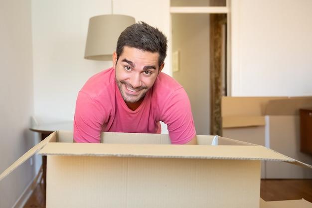 Jovem alegre desempacotando coisas em seu novo apartamento, abrindo a caixa de papelão,