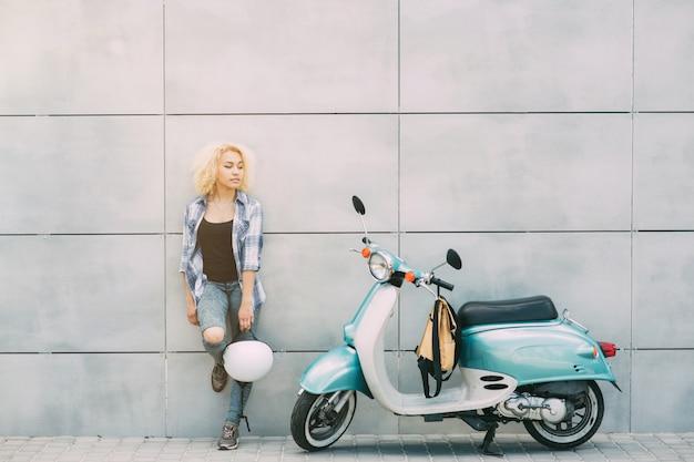 Jovem alegre dirigindo o scooter na cidade. retrato de uma mulher jovem e elegante, com um ciclomotor