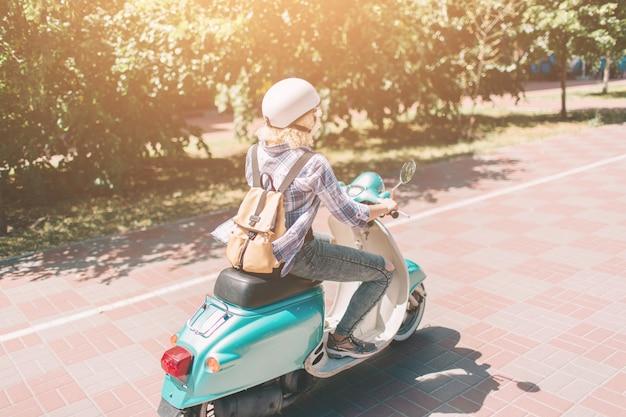 Jovem alegre dirigindo scooter na cidade