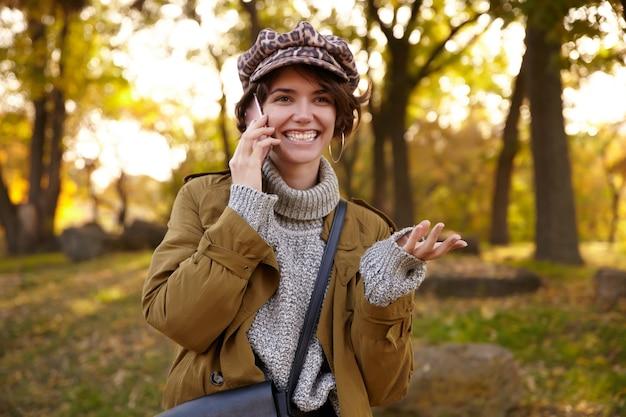 Jovem alegre e adorável mulher de cabelos castanhos com penteado casual vestindo roupas elegantes enquanto caminha pelo jardim da cidade, sorrindo alegremente e mantendo a mão levantada enquanto tem uma conversa agradável