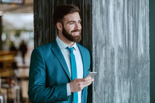 Jovem alegre e ambicioso empresário caucasiano vestido de terno azul, apoiando-se no pilar, segurando o telefone inteligente e desviar o olhar.