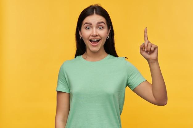 Jovem alegre e animada com cabelo escuro e camiseta menta segurando uma iseda e apontando para cima com o dedo sobre a parede amarela