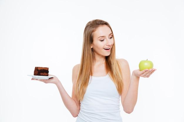 Jovem alegre e animada escolhendo entre comida saudável e não saudável, sobre fundo branco