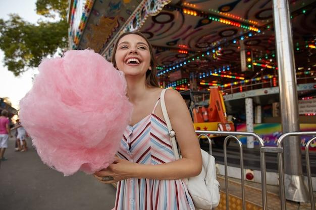 Jovem alegre e atraente morena com cabelo comprido andando pelo parque de diversões, usando um vestido de verão e segurando algodão doce no palito, olhando para o lado e rindo feliz