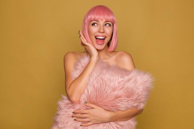 Jovem alegre e atraente mulher de cabelo rosa com manicure verde olhando alegremente para o lado e mantendo a boca bem aberta, segurando um travesseiro fofo sobre a parede de mostarda