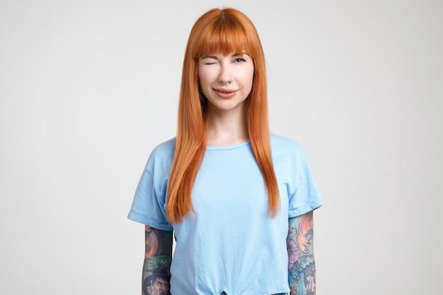 Jovem alegre e atraente tatuada com cabelo solto de raposa dando uma piscadela positiva para a câmera em pé sobre um fundo branco com as mãos ao longo do corpo