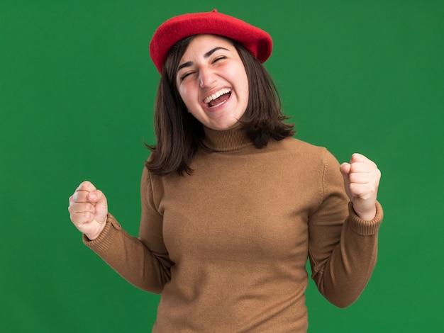 Jovem alegre e bonita caucasiana com chapéu boina mantém os punhos isolados na parede verde com espaço de cópia