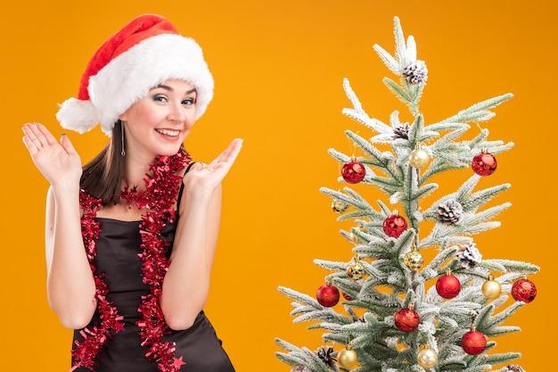 Jovem alegre e bonita caucasiana com chapéu de papai noel e guirlanda de ouropel no pescoço, em pé perto da árvore de natal decorada, mostrando as mãos vazias isoladas na parede laranja