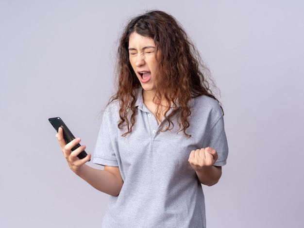Jovem alegre e bonita caucasiana segurando um celular, fazendo um gesto de sim com os olhos fechados