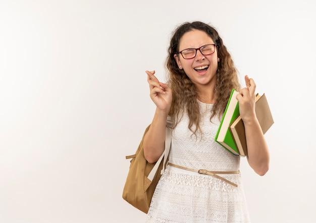 Jovem alegre e bonita colegial de óculos e mochila segurando livros e cruzando os dedos com os olhos fechados, isolado no branco