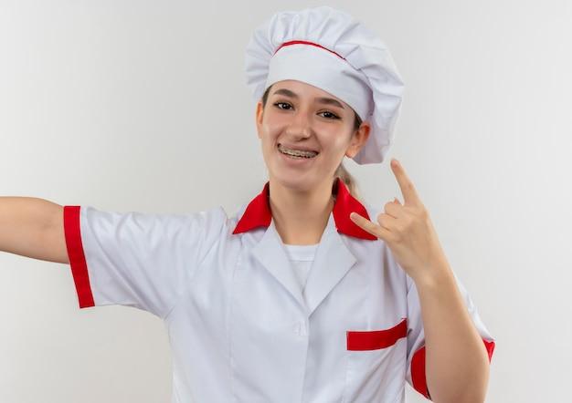 Jovem alegre e bonita cozinheira em uniforme de chef com aparelho dentário e braço aberto fazendo sinal de pedra na parede branca