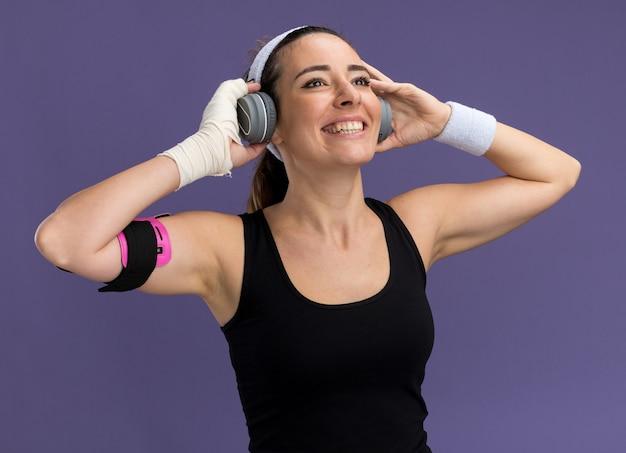Jovem alegre e bonita e esportiva usando pulseira, fones de ouvido e uma braçadeira de telefone com o pulso ferido enrolado em uma bandagem olhando para cima agarrando os fones de ouvido