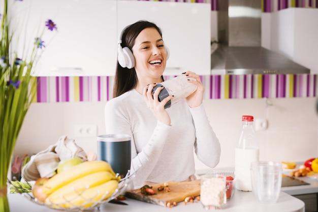 Jovem alegre e bonita está agitando sua tigela shaker cheia de ingredientes de smoothie enquanto tocando música em seus fones de ouvido na cozinha brilhante.