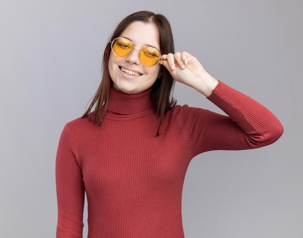 Jovem alegre e bonita usando e agarrando óculos de sol