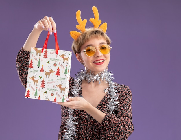 Jovem alegre e bonita usando uma bandana de chifres de rena e uma guirlanda de ouropel em volta do pescoço, com óculos segurando uma sacola de presente de natal, olhando para a câmera isolada no fundo roxo