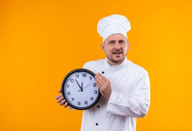 Jovem alegre e bonito cozinheiro em uniforme de chef segurando um relógio isolado na parede laranja