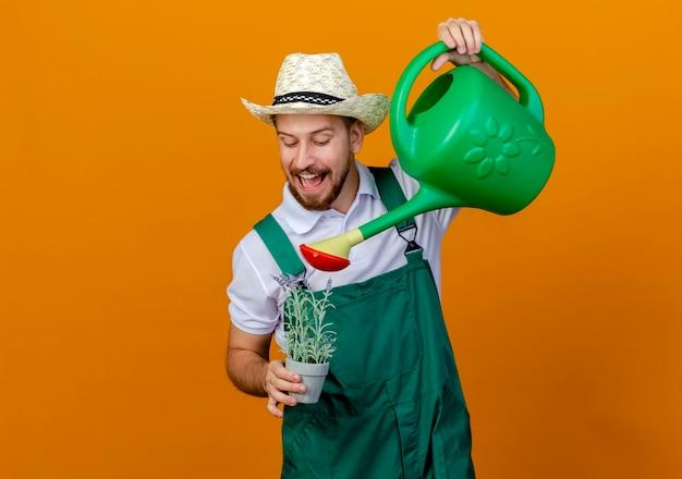Jovem alegre e bonito jardineiro eslavo de uniforme e chapéu segurando um vaso de flores e regando-o com um regador isolado