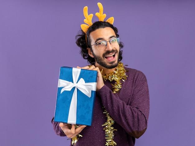Jovem alegre e bonito usando uma argola de cabelo de natal com uma guirlanda no pescoço e segurando uma caixa de presente isolada sobre fundo azul