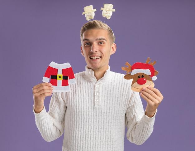 Jovem alegre e bonito usando uma faixa de boneco de neve segurando um casaco de papai noel de natal e enfeites de papel de rena olhando para a câmera isolada no fundo roxo