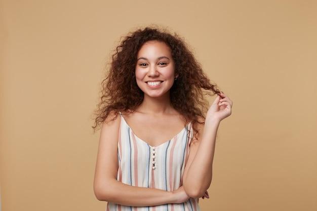 Jovem alegre e charmosa morena encaracolada puxando o cabelo com a mão e parecendo feliz com um largo sorriso, isolado no bege