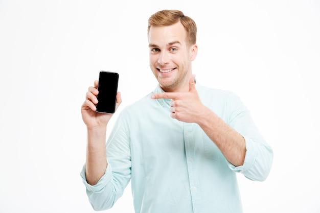 Jovem alegre e confiante mostrando um celular com tela em branco sobre uma parede branca