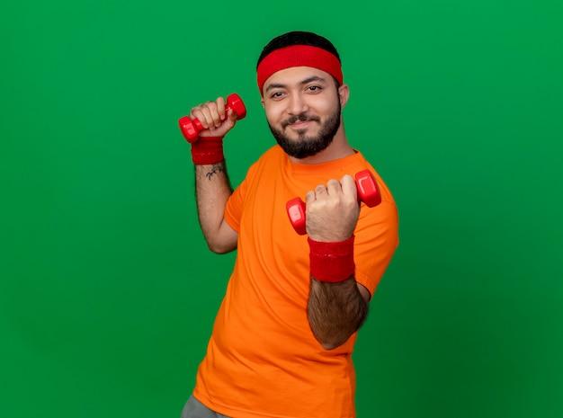 Jovem alegre e esportivo usando bandana e pulseira, fazendo exercícios