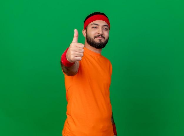 Jovem alegre e esportivo usando bandana e pulseira mostrando o polegar isolado no verde