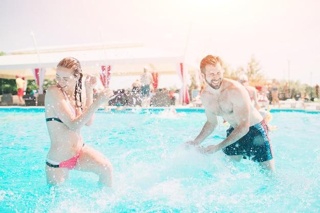 Jovem alegre e jovem descansando na piscina ao ar livre