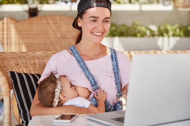 Jovem alegre e linda mãe trabalha como freelance em casa, faz trabalho remoto para ganhar mais dinheiro estando de licença maternidade