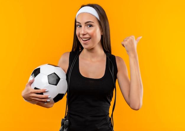 Jovem alegre e muito esportiva usando bandana e pulseira, segurando uma bola de futebol e apontando para o lado com uma corda para pular em volta do pescoço