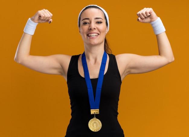 Jovem alegre e muito esportiva usando bandana e pulseiras com medalha em volta do pescoço fazendo um gesto forte isolado na parede laranja