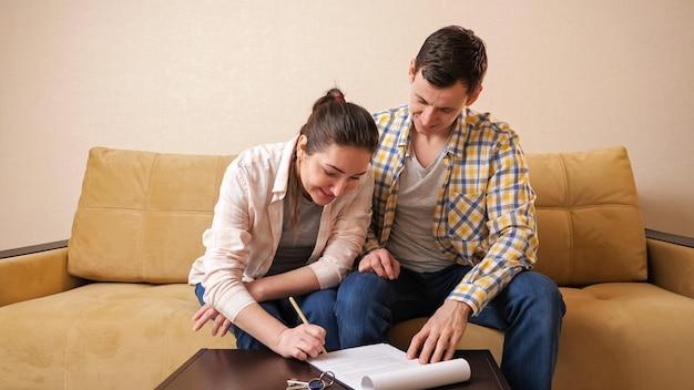 Jovem alegre e mulher assinam contrato de aluguel de apartamento em uma pequena mesa de centro, sentados em um sofá confortável em um escritório contemporâneo
